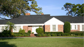 Ranch style home. Red brick home with white trim, ranch style stock image