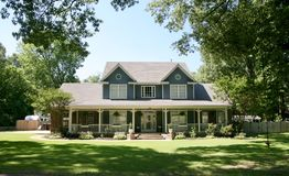 Ranch Style Home. A two-story Ranch style home shaded beneath trees royalty free stock images