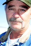 Rancher. A closeup portrait of a working middle aged rancher with a full mustache, wearing a bill cap. shallow depth of field Stock Image