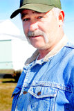 Rancher Man. A closeup of a working middle aged rancher with a full mustache, wearing a bill cap with barn in background. shallow depth of field Stock Images