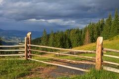 Rancho de madeira da cerca que negligencia a paisagem da montanha imagem de stock