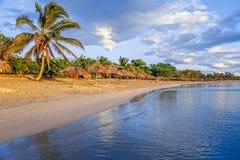 Rancho Luna g?mma i handflatan den karibiska stranden med och sugr?rparaplyer p? kusten, Cienfuegos, Kuba arkivbilder
