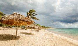 Rancho Luna g?mma i handflatan den sandiga stranden med och sugr?rparaplyer p? kusten, Cienfuegos, Kuba royaltyfri foto