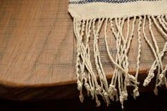 Rand der hölzernen Tabelle mit einem schlichten Tuch Stockfotografie