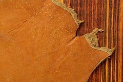 Rand des Schafleders im orange Farbton auf dem Holztisch lizenzfreie stockbilder