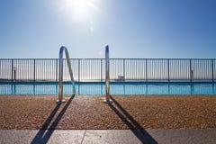 Rand des Swimmingpools mit Sonnenaufflackern im Hintergrund Stockbilder