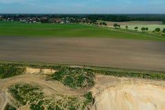 Rand van een zandsteengroeve, van het dorp door een akkerland, mijnbouw wordt gescheiden die royalty-vrije stock foto's