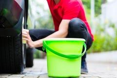 Rand van het mensen de schoonmakende wiel terwijl autowasserette Stock Foto's