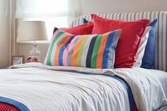 Randig huvudgavel med Colourfull kuddar och den gjorde randig kudden på vit säng arkivfoton