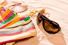 Randig strandhandduk och solglasögon på en sandig strand Royaltyfri Foto