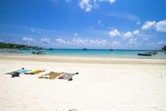 Randig strandhandduk på den härliga stranden med den nya blåa himlen, på den Samed ön i Thailand Resa resväskan med seascapeinsid Royaltyfri Bild