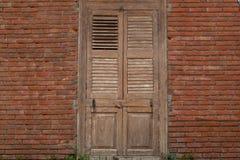 Randiga tegelstenväggar och trädörren används som bakgrunden arkivfoton