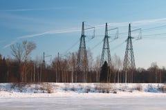 Randigt landskap - is på floden, kraftledningen och den blåa himlen Royaltyfri Bild