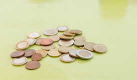 Random amount of euro coins. On green table royalty free stock images