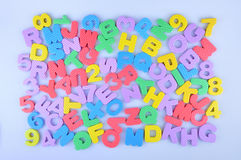 Random colorful English alphabet and numbers. Colorful English alphabet and numbers randomly  on a light blue background Royalty Free Stock Image