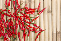Random fresh red chili on stripe bamboo wood. Background Royalty Free Stock Photos