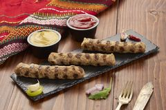 Grilled Veal minced meat with spices on black stone and wooden background royalty free stock image