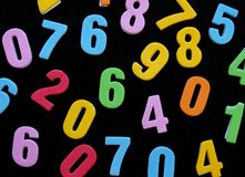 Random numbers. Black surface covered with multiple colorfull toy numbers Stock Photography