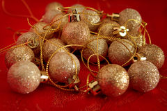 Random pile of gold glitter christmas baubles. A random pile of gold glitter mini Christmas baubles on a red festive background Royalty Free Stock Images