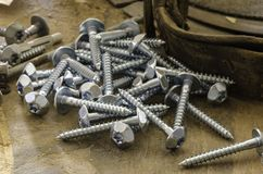 Random pile of hexagonal threaded steel bolts or screws. Royalty Free Stock Photography