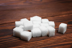 Random pile of sweet sugar cubes on a dark brown wooden table. Refined white sugar on the table. Few pieces of sugar cubes. stock photo