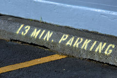 Random Time Limit. S parking to 13 minutes. Concrete curb has stenciled lettering and numbers in yellow spray paint stock photography