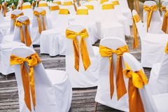 A group of white spandex chairs cover with gold organza sash for beach wedding venue arrangement. The random white spandex chairs cover with gold organza sash Stock Photography