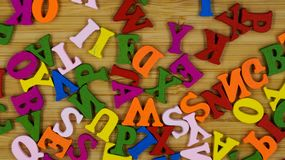 Randomly scattered colorful wooden letters on a wooden background. royalty free stock image