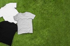 Randomly scattered mens different coloured T-shirts on grass background. Horizontal view royalty free stock photos