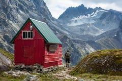 Randonneur à côté de hutte de région sauvage en montagnes de Talkeetna, Alaska Image stock