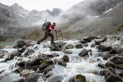 Randonneur avec le grand paquet traversant une rivière rocheuse Photographie stock libre de droits