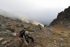 Randonneur avec le sac à dos entrant en montagnes photographie stock