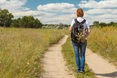 Randonneur avec le sac à dos marchant sur la route rurale Images libres de droits