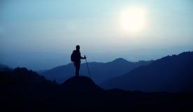 Randonneur avec le sac à dos se tenant sur la colline Image libre de droits