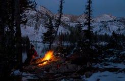 Randonneur chaud lui-même à un feu de camp une nuit froide d'hiver Photo libre de droits