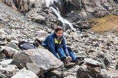 Randonneur détendant aux montagnes Photographie stock