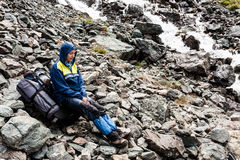 Randonneur détendant aux montagnes Image stock