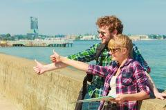 Randonneur de couples avec la carte par le bord de la mer faisant de l'auto-stop Image libre de droits