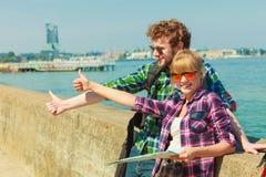Randonneur de couples avec la carte par le bord de la mer faisant de l'auto-stop Photographie stock libre de droits