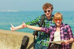 Randonneur de couples avec la carte par le bord de la mer faisant de l'auto-stop Images libres de droits