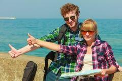 Randonneur de couples avec la carte par le bord de la mer faisant de l'auto-stop Images stock