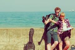 Randonneur de couples avec la carte par le bord de la mer faisant de l'auto-stop Photos stock