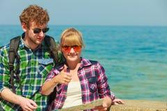 Randonneur de couples avec la carte par le bord de la mer Images libres de droits
