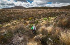Randonneur de femme avec le sac à dos marchant à pas marqués sur le parc national de Tongariro photographie stock libre de droits