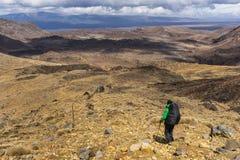 Randonneur de femme avec le sac à dos marchant à pas marqués sur le parc national de Tongariro photographie stock