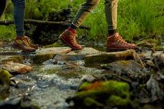 Randonneur de femme croisant un petit courant de forêt Photo libre de droits