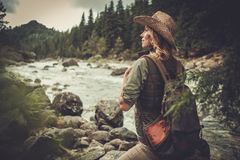 Randonneur de femme marchant près de la rivière sauvage de montagne Photographie stock
