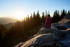 Randonneur de femme s'asseyant sur le rocher dans les montagnes au coucher du soleil photographie stock libre de droits