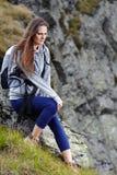 Randonneur de femme se reposant sur une roche Photo stock