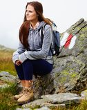Randonneur de femme se reposant sur une roche Photographie stock libre de droits